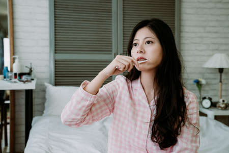 portrait of asian woman with morning feature is brushing teeth and gazing into distance. taiwanese girl washing up holding toothbrush, not quite sober up. daily routine and lifestyle