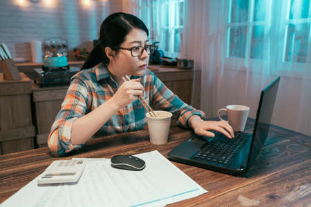 Young asian chinese female at laptop computer eats instant ramen noodles late in evening. Woman in glasses studying online overtime at night has fast dinner. concept unhealthy junk food at workplace Imagens