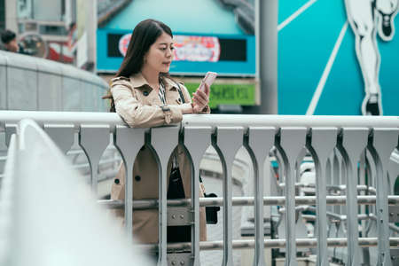 asian chinese woman using smartphone in osaka city japan.