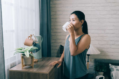 asian sportive woman standing by window placing hand on cupboard is having drink after workout.