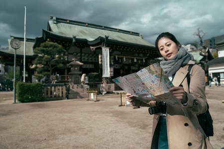 Young woman traveler with backpack and camera looking paper map in tenmangu shrine in osaka japan.