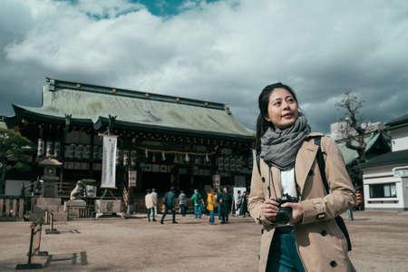 asian female photographer travel sightseeing in tenmangu shrine in osaka japan overcast.
