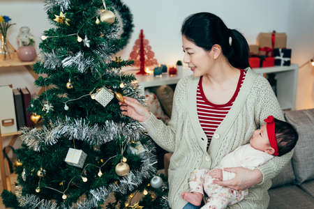 portrait pretty korean lady holding a newborn baby is standing by a christmas tree. asian mom looking at a golden ornament with a smile. genuine lifestyle Zdjęcie Seryjne