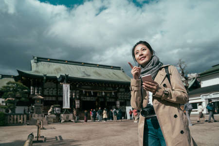 Cheerful beautiful young Asian backpacker blogger woman using smartphone searching tourist attraction location while travel in osaka. Zdjęcie Seryjne