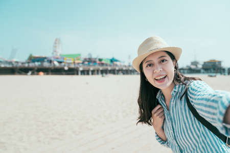 freedom young asian japanese female backpacker wear straw hat standing on beach with blue sky. woman photographing selfie with amusement park and sea on sunny day. lady face camera make self portrait
