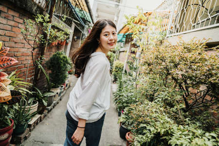 young beautiful asian japanese girl walking in little walkway surrounding by red brick old house in town of taichung taiwan. charming female face camera smiling in lane by plants on road on sunny day