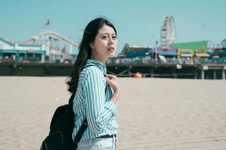 beautiful asian japanese woman backpacker walking on sandy beach outdoor on sunny day. side view of young relax charming female tourist with bag enjoy ocean with blurred amusement park in background.
