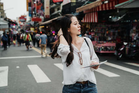 travel lifestyle of happy asian chinese woman. traveler young girl standing on holiday festival outdoor famous local street market with paper map. charming lady searching direction way on road Zdjęcie Seryjne