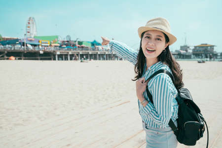 Beautiful young woman with backpack having fun at amusement park. relaxation in spring sandy beach concept. pretty girl traveler in straw hat looking face camera smiling point theme park on sunny day Zdjęcie Seryjne