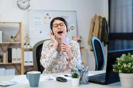 Young woman fashion designer in earphones sitting at desk amazedly using cellphone singing at work in modern office. happy female tailor in headphones and holding mobile phone as microphone in studio