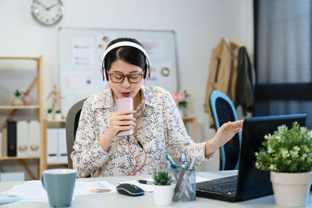 beautiful woman tailor singing and listening to music with headphones at workshop. Young asian female freelancer sitting in work desk and holding smartphone as microphone carefree in modern office.