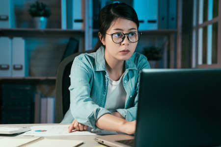 Young beautiful woman freelance using laptop computer at night. concentrated girl worker in glasses typing on keyboard notebook pc in home office in midnight. elegant female employee overtime working