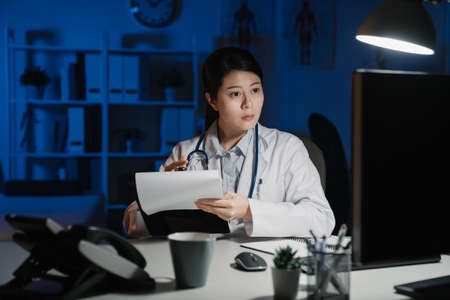 young medical industry employee writing in notebook while sitting in dark modern clinic office. Confident asian korean female doctor holding pen making note on notepad in late night hospital.