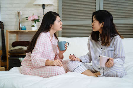 Surprised asian japanese ladies sitting bed and looking at each other with shocked face while listening news chatting gossip. Amazed girls in pajamas sharing problems with cup of coffee in bedroom