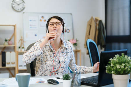 Office life rhythm regular concept. startup businesswoman in headphones sit office listen music sing song. female worker with cellphone begin working day with favorite song in modern workplace