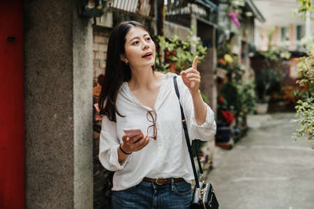 young asian korean attractive lady searching hostel in historical old town and point on door number plate. cute female traveler holding cellphone finding direction in lane with flowers and plants.