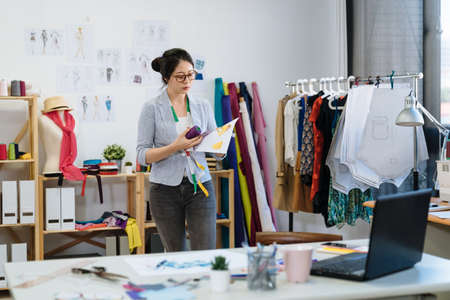 young professional female dressmaker holding sewing accessories with sketch draws in hands and walking in office. lady fashion designer in studio choosing purple kit for new autumn season clothes Zdjęcie Seryjne