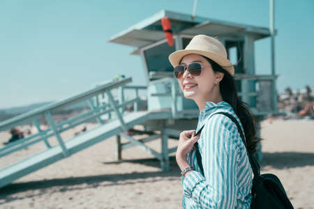 bokeh view lifeguard tower in Santa Monica on sunny day in California USA. happy smiling young girl traveler with backpack wearing straw hat and sunglasses standing on sandy beach by safeguard stand