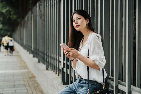 Attractive young travel woman with smartphone in city park. charming asian lady using mobile phone on street. happy smiling girl using modern cellhone outdoors while leaning on railing on walkway Zdjęcie Seryjne