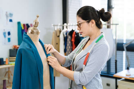 female fashion designer standing next dummy model and adjusting new seasonal clothes. young girl staff in workshop with measure tape on shoulder and fixing scarf on mannequin. creative work concept