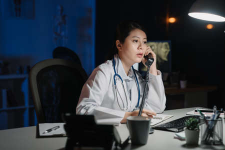 Young practitioner doctor working at 24h open clinic. asian japanese female nurse answering phone calls in late night hospital. medical staff discussing and solve problem in dark workplace midnight