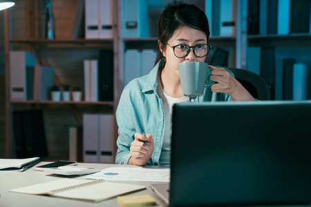 Shot of young asian korean businesswoman drinking cup of hot coffee and working at home office. beautiful lady freelance in glasses holding a mug in hand sitting at workplace in apartment in midnight Zdjęcie Seryjne