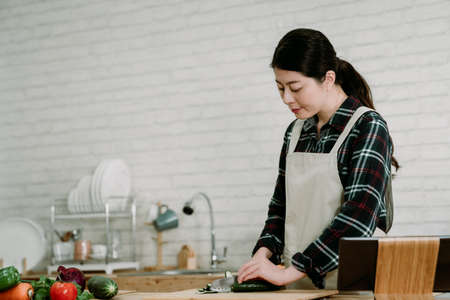 young elegant asian korean woman in modern kitchen following recipe online website on digital tablet. smiling wife in apron chopping cucumber with sharp knife on wooden cutting board in cooking place Zdjęcie Seryjne
