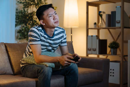 Young handsome man playing with video game joystick controller in late night home living room with sad expression. upset guy sitting on sofa with lose on online entertainment in evening in apartment. Zdjęcie Seryjne