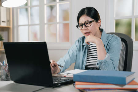 attractive asian korean female university student using laptop in house. pensive young college girl thinking solution about project for final exam. thoughtful lady hard working on notebook in home. Zdjęcie Seryjne