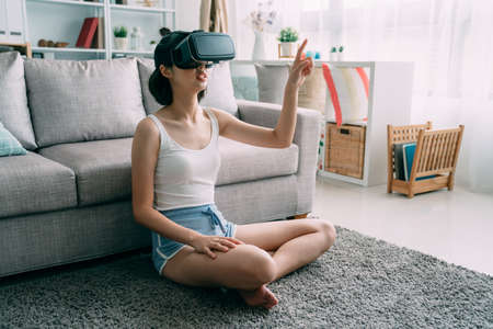charming asian korean woman in shorts using new virtual reality headset sitting on carpet on floor in modern apartment. young girl in vr goggles in living room at home having fun. female point finger