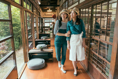 travel lifestyle moments in traditional japanese house. full length group young female tourists wearing socks walking on wooden floor inside ancient wood building. women together looking outdoors