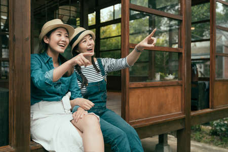 two cheerful young asian chinese girl travelers pointing finger away while relax sitting on wooden floor. friends in straw hats smiling enjoy garden view from japanese traditional design house.