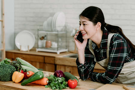 Shot of pretty young asian korean woman talking on mobile phone while leaning on counter table with fresh vegetables in kitchen at home. smiling girl in apron chatting on cellphone in cooking place