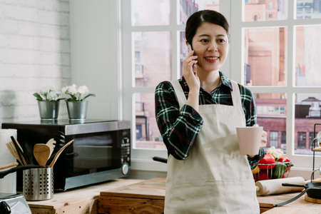 Beautiful girl talking on mobile phone holding cup of tea looking away and smiling while standing at table in kitchen. happy woman in apron drinking coffee and having cellphone conversation indoors