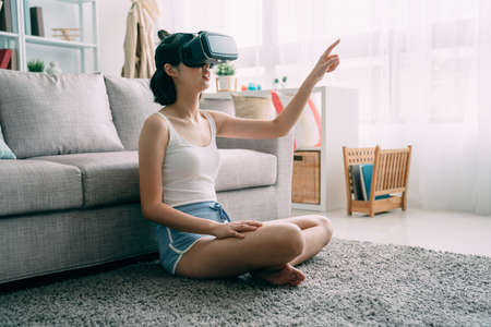 young cute asian japanese woman sit on carpet at home wearing virtual reality headset in home living room. charming girl in shorts in vr goggles point finger in house. lady on floor enjoy 3D glasses Zdjęcie Seryjne