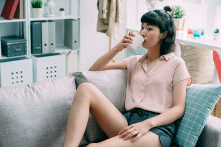Portrait of asian chinese charming woman holding cup of tea looking away. young girl leaning lying on comfort sofa drinking beverage. cute female enjoy coffee in morning sitting on couch in cozy home Zdjęcie Seryjne