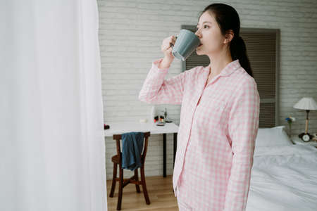 taiwanese lady standing straight holding mug is bathing in natural light looking afar outside window. asian female with the habit of drinking a cup of warm water every morning after getting up. Zdjęcie Seryjne