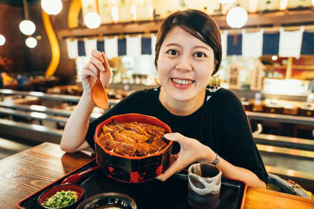 rice bowl topping with grilled japanese freshwater eel with Teriyaki sauce. young charming asian korean lady traveler experience japan culture try local meal food. girl face camera smile show unadon Zdjęcie Seryjne