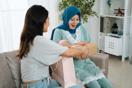 Happy pregnant islam woman with female friend at baby shower. Expectant motherhood sitting on sofa and receiving gift box during her baby shower. asian sister sending present to maternity lady
