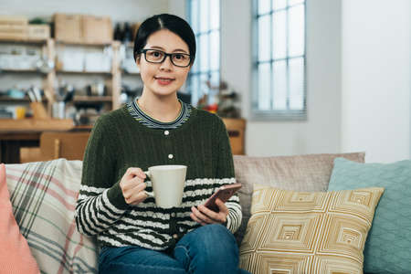 asian lady face to camera with smile is sitting elegantly with morning coffee while using mobile. beautiful chinese woman laying hand on knee is enjoying drink while using her smartphone in house. Zdjęcie Seryjne