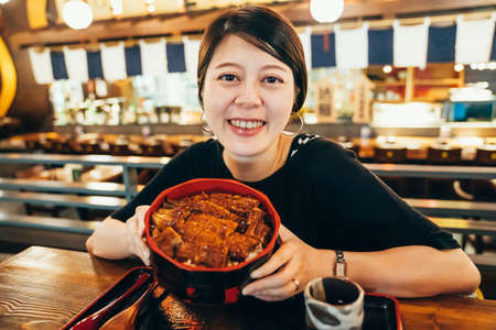 Soy sauce Japanese food to grilled eel. confident beautiful young asian chinese woman visiting izakaya and sitting at wooden table face camera smiling. happy girl showing bowl of unadon fish rice. Zdjęcie Seryjne