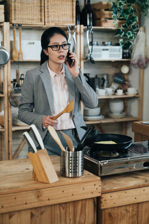 busy chinese career woman holding wooden spoon stops cooking meal to answer phone call from work in the kitchen. asian businesswoman is discussing important project on phone when preparing breakfast.