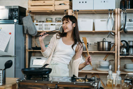 Happy Asian Japanese holding the chopstick and spatula dancing in the kitchen, enjoy the relaxation morning.