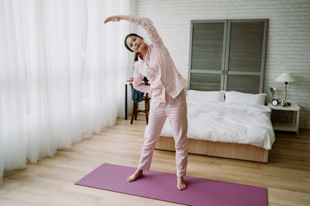 full length smiling chinese female in pajamas stretching with her right arm akimbo. asian millennial woman warming up body after getting up. daily routine and lifestyle