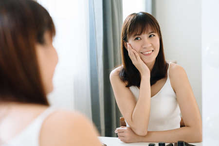 beautiful japanese girl is looking at her reflection in front of mirror with pleasant expression. young female touching her cheeks is feeling confident about her smooth skin and good complexion. Zdjęcie Seryjne