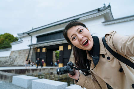 happy young lady holding camera is taking a selfie with smartphone at the entrance of Nijo Castle. asian female traveler facing to camera is excited to see the famous historic building in Japan. Zdjęcie Seryjne