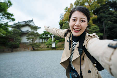 asian travel channel host spreading arm is introducing a cultural heritage in Kyoto to audience. cheerful youtuber is sharing her trip with her followers on arriving at the famous historic site.