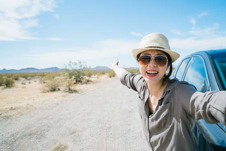 asian woman by car having jolly laugh is taking selfie with wild nature in desert region. female visitor taking photo background open land with clumps of bush and azure sky. summer grand tour concept Zdjęcie Seryjne