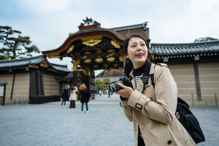 korean visitor with camera is standing in front of Karamon gate of Nijo Castle and looking around excitedly. asian female tourist carrying camera is thrilled to visit famous historic site in person. Zdjęcie Seryjne