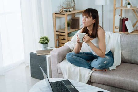 asian woman is holding a mug and taking a break on a holiday morning. pretty lady is looking out the window enjoying her tea and the refreshing morning.